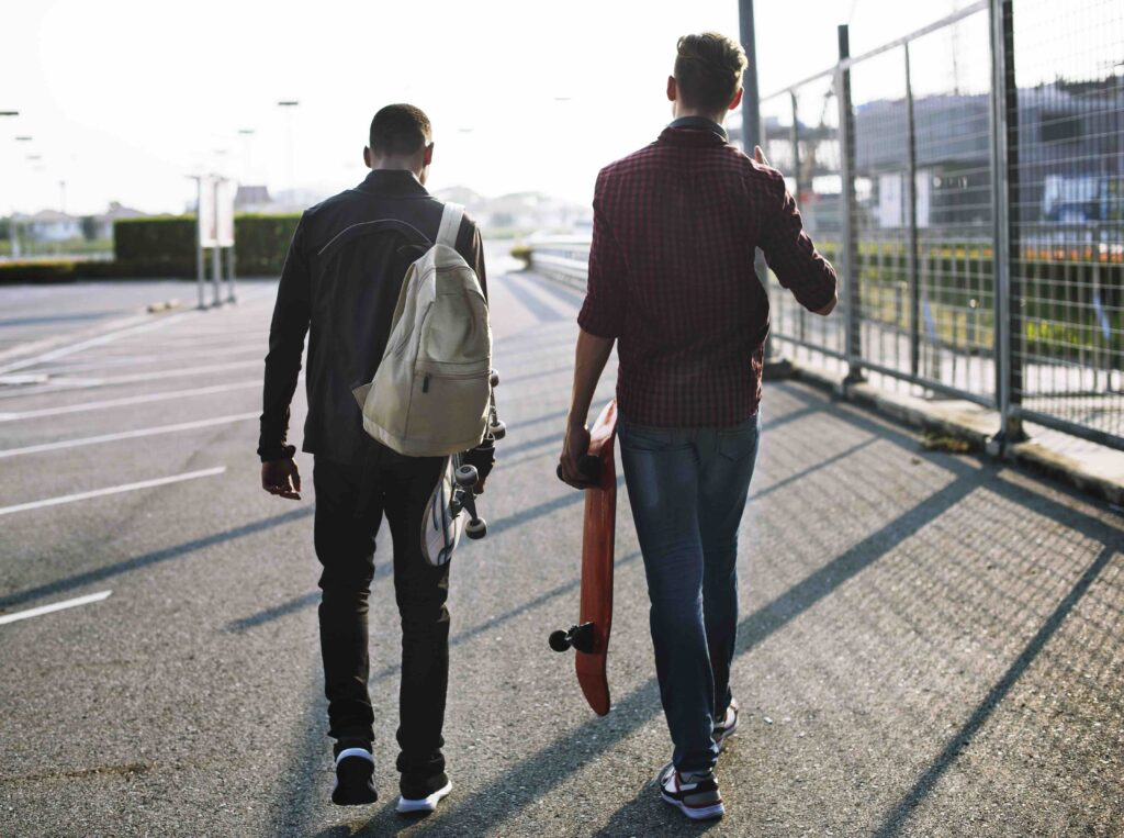 Two teenager boys walking with skateboards