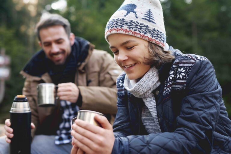 Close up of smiling teenage boy drinking tea in forest