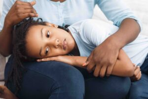 Black daughter lying her head on mom's lap